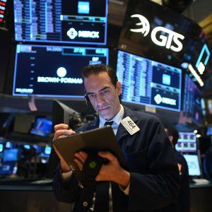 En man i kostym står framför en mängd skärmar på New York-börsen den 19 mars 2020.