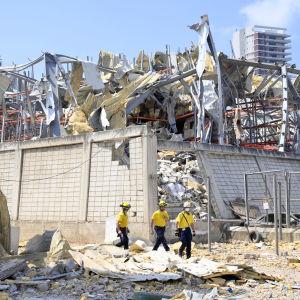 Människor letar i ruinerna av byggnad.