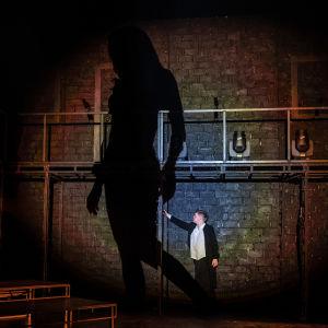 En man står på en teaterscen, en stor mörk skygga bredvid sig.