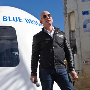 Jeff Bezos med solglasögon framför Blue Origins rymdkapsel 2017.