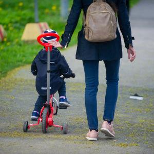 En kvinna som hjälper ett litet barn att cykla, bilden tagen bakifrån.