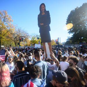 Demonstranter firar Kamala Harris med en utklippt figur av papp som föreställer henne.