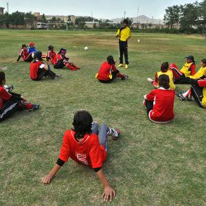 Afganistanilaiset tytöt kuuntelevat valmentajan neuvoja.