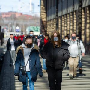 Resenärer med munskydd på perrongen vid Helsingfors järnvägsstation.