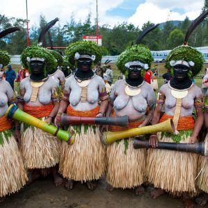 Värikkäästi pukeutuneita ja kehomaalattuja naisia traditonaalisessa Sing Sing -juhlassa