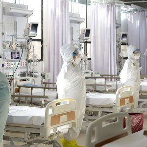 sjukvårdare i skyddsutrustning står bredvid sängar i ett sjukhus