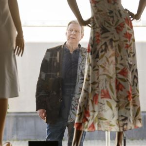 Rolf Lassgård står ute på gatan och tittar in på blommiga klänningar genom ett skyltfönster.