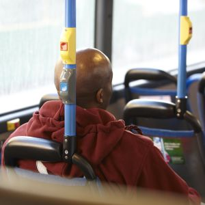 En flintskallig mörkhyad man sitter med ryggen till i lokalbussen.