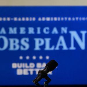 """Joe Biden håller tal. I bakgrunden syns en plansch med texten """"American Jobs Plan""""."""