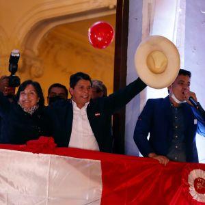 Pedro Castillo ja Dina Boluarte vilkuttavat parvekkeelta tukijoilleen Perussa 19. heinäkuuta 2021.