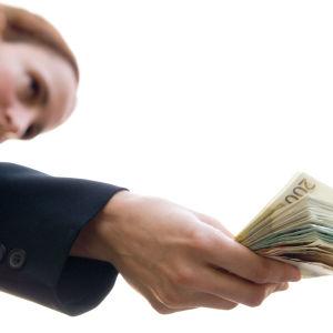 Kvinna räcker över fler euro-sedlar.