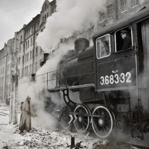 Skådespelaren Maksim Sukhanov står bredvid ett ångande lok på en järnvägsstation.