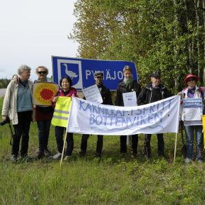 Gruppfoto på rikssvensk kärnkraftsdemonstraner med banderoll och flaggor i Pyhäjoki invid Europaväg 8.