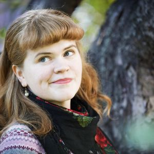 ung kvinna med pärlörhänge leende från sidan blickar åt sidan