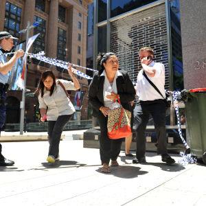 Polisen släpper fotgängare förbi en avspärrning under ett pågående gisslandrama i Martin Place i centrala Sydney.