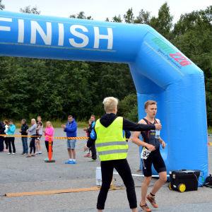 Den vinnande triathleten i sprintsträckan i sun city triathlon kommer i mål. Han erbjuds vattenflaska av en funktionär.