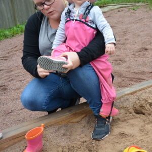 En dagistant klär på stövlar på ett barn i sandlådan.