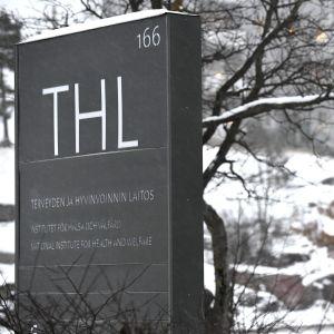 En skylt med texten THL i ett vinterlandskap.