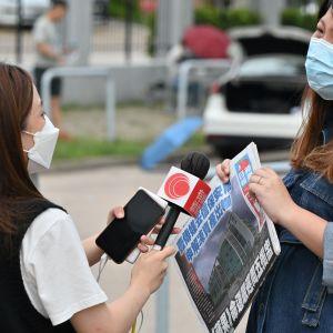 En reporter från Apple Daily intervjuar en person som stöder tidningen utanför Apple DAilys högkvarter.
