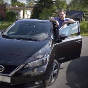 en man står lutad vid dörren på sin svarta elbil och ser mot kameran