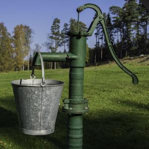 En gammaldags vattenpump med en plåthink som hänger.