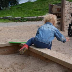 Ett litet barn, cirka två år gammalt, kliver ut ur en sandlåda.