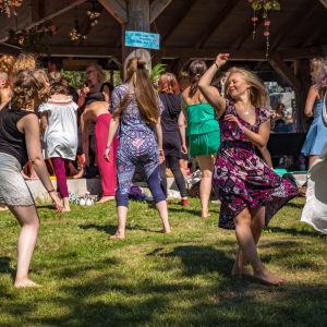 Flera människor dansar på en gräsmatta.