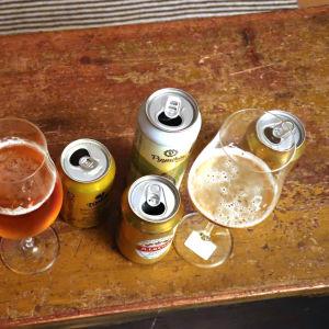 Ölglas och ölburkar på ett brunt bord.