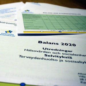 En hög med utredningar där det står Balans 2020 på pappren.