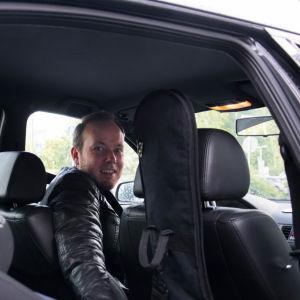Mikael Grönroos i bilen bakom ratten tittar över axeln mot kameran genom bakdörren som är öppen.
