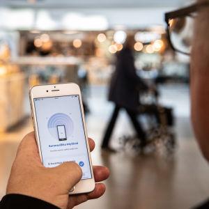 En mobiltelefonen i handen på en person. På skärmen visas appen Coronablinkern.