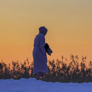 Henkilä aamutakki päällä kävelemässä avannosta pukukoppiin talvipakkasella auringonlaskun värjäten taivaan oranssiksi.