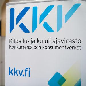 En närbild på en skylt med texten KKV, Konkurrens- och konsumentverket. I bakgrunden syns en människa som går längs KKV:s korridorer.