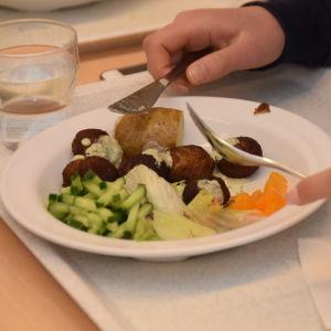 En tallrik med skolmat som består av fiskbullar och potatis.