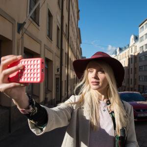 Donna (Alina Tomnikov) står på gatan och håller en telefon med framsträckt hand framför ansiktet. Solen skiner i ansiktet på Donna och i bakgrunden syns bilar.