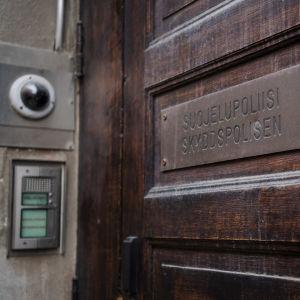 Bastant ytterdörr till Skyddspolisens högkvarter i Helsingfors, med övervakningskamera utanför.