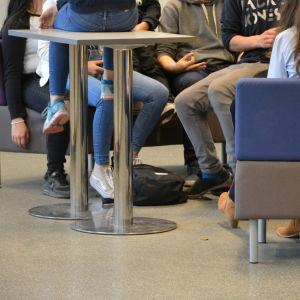 Bild av ungdomars fötter och ben i en soffa.