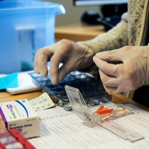 Kotihoitaja annostelee lääkkeitä dosettiin