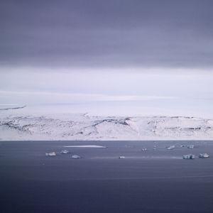Utsikt från Thulebasen: Fiskebåtar på fjorden, med grönländska fjäll i bakgrunden.