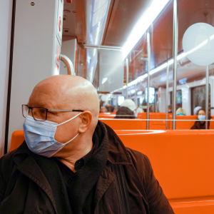 Kaljupäinen mies metrossa kasvomaski kasvoillaan.