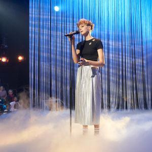 Tyra med blålila bakgrund och rök på scenen.