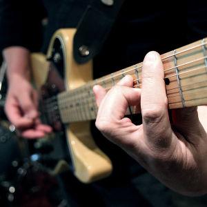 Valokuva haastateltavasta soittamassa kitaraa