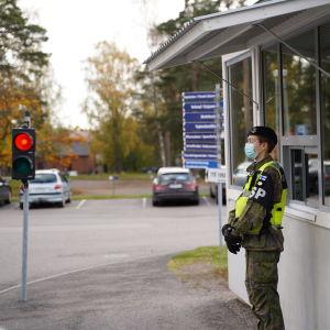 En person i unifrom står med munskydd på sig vid ett vaktbås, I bakgrunden ett trafikljus som visar rött. Det är höst för löven är gula.