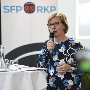 Anna-Maja Henriksson talar i en mikrofon stående vid ett barbord.