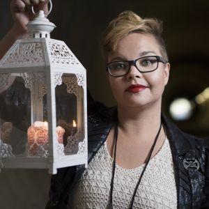 Kirjailija Salla Simukka kynttilälyhty kädessään