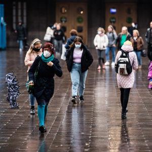 Många människor promenerar åt olika håll, med stora bruna dörrar i bakgrunden. Utanför Helsingfors järnvägsstation den 27 oktober 2020.