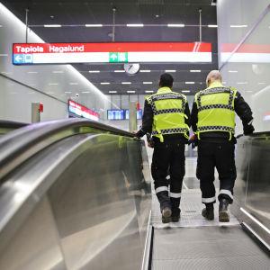 Kaksi vartijaa metroaseman liukuportaissa.