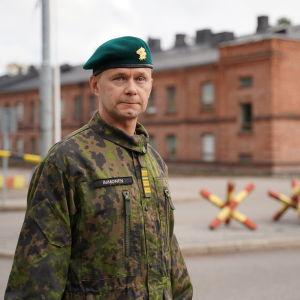 En man i uniform och en namnbricka med namnet Immonen ser allvarligt in i kameran. I bakgrunden ett stort tegelhus i kasernstil.