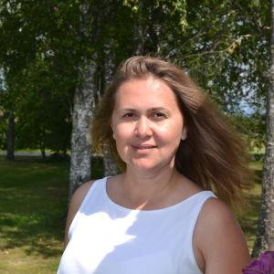 Natali Panchuk står ute på sin gård i Sibbo. I bakgrunden skymtar hennes hus och hörnet av en hängmatta.