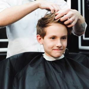 Ung kille blir klippt i en barberarstol.